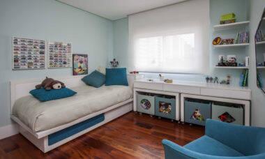 Neste quartinho projetado pela arquiteta Karina Korn, nada de tapetes que possam oferecer o risco de quedas. Com um espaço confortável de circulação no centro do cômodo, a criança pode acessar os brinquedos dispostos nas caixas com rodinhas, facilitando o momento de brincar | Foto: Eduardo Pozella