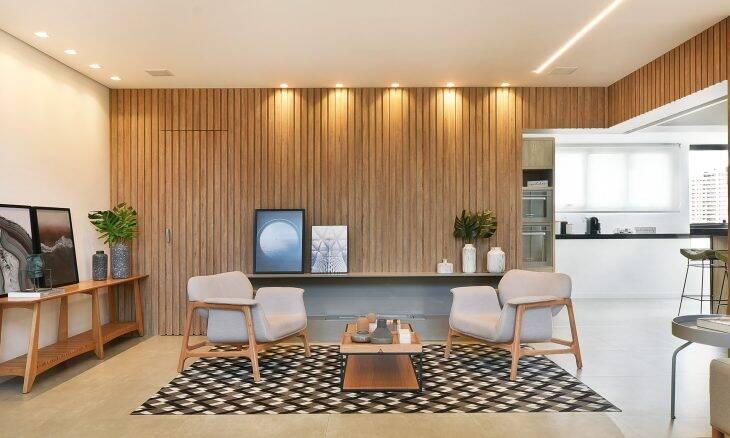 Neste projeto da arquiteta Marina Salomão, as molduras escuras dos quadros apoiados no aparador e bancada suspensa contrastam com o tom claro da madeira presente em todos os móveis e o efeito ripado, que reveste parede e porta camuflada | Foto: Sidney Doll