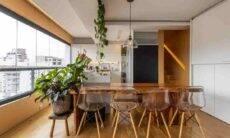 Na sala de jantar, o paisagista Luciano Zanardo criou diversos pontos de área verde. No banco de madeira, foram utilizados vasos com a filodendro rubro, filodendro ondulatum e fícus lyrata. Para forma essa cortina verde, logo acima da mesa, a filodendro-cordato | Foto: JP Image