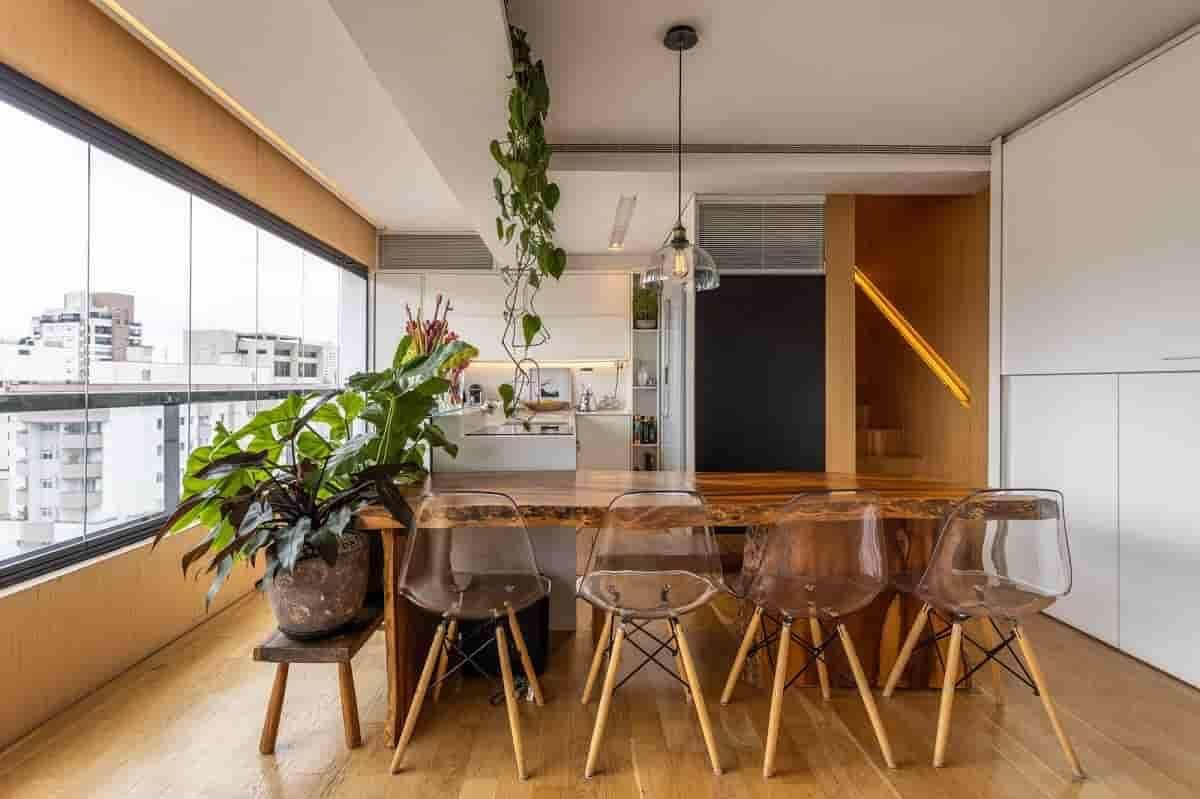 Na sala de jantar, o paisagista Luciano Zanardo criou diversos pontos de área verde. No banco de madeira, foram utilizados vasos com a filodendro rubro, filodendro ondulatum e fícus lyrata. Para forma essa cortina verde, logo acima da mesa, a filodendro-cordato   Foto: JP Image