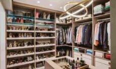 No closet do casal, as profissionais da Meet Arquitetura dedicaram um espaço generoso para a disposição dos calçados e a coleção de bolsas. Ao centro, um móvel foi projetado para expor os objetos da moradora, com direito a uma 'vitrine' para a visualização das joias e uma luminária moderna | Foto: Henrique Ribeiro