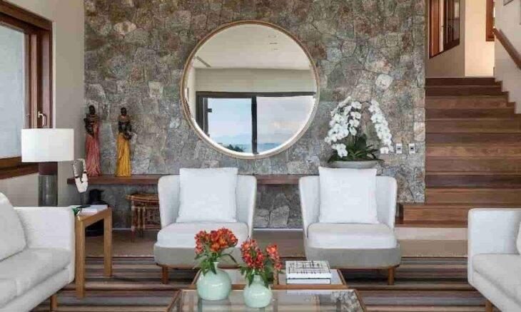 O grande espelho redondo compõe a parede deste living que foi revestida com a atmosfera rústica da pedra moledo | Projeto do escritório Corradi Mello Arquitetura | Foto: Evelyn Müller