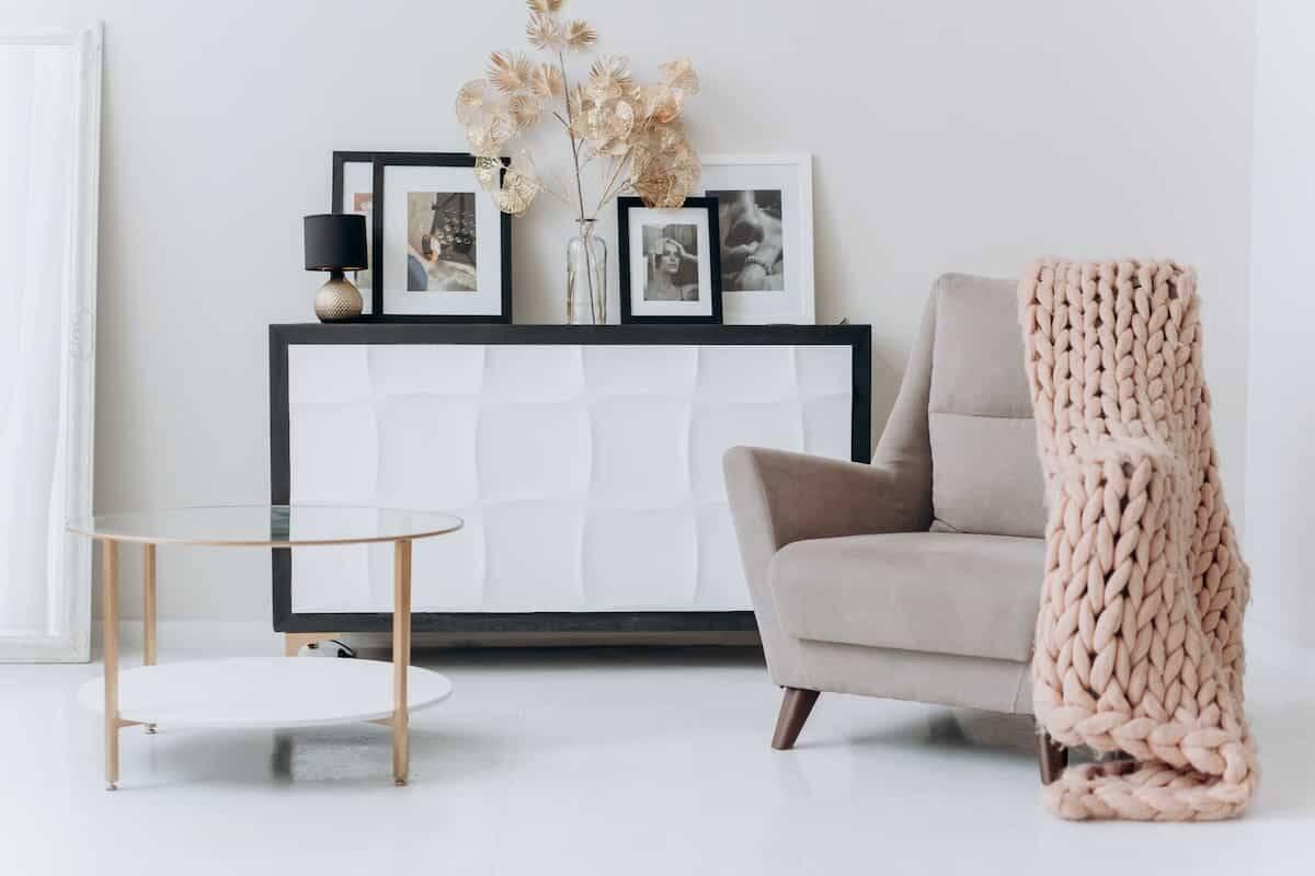 Tendências de decoração para 2022. Na foto, vemos o estilo minimalista, com uma mesa de apoio redonda e textura de tecido natural nas folhagens e na manta sobre a poltrona. Foto: Mikhail Nilov