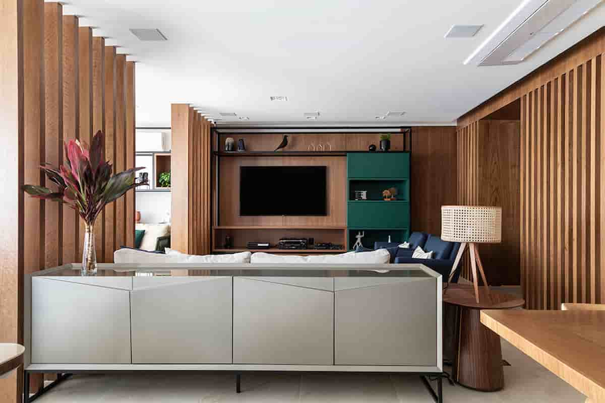 Na sala de estar conectada ao jantar, a arquiteta Marina Carvalho explorou as costas do sofá para instalar um buffet que organiza os itens utilizados pelos moradores |Fotos: Evelyn Müller