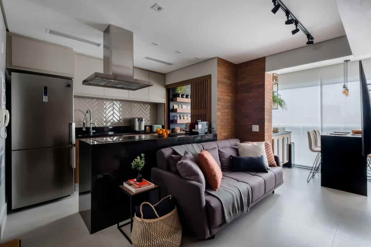 Neste apartamento de 120m², as arquitetas do Mirá Arquitetura o granito São Gabriel para revestir a ilha da cozinha. A cor faz uma relação direta com o estilo industrial adotado para todo o projeto  Foto: Nathalie Artaxo