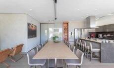 Alocada entre o living e o espaço gourmet, essa sala de jantar, assinada pela arquiteta Patricia Penna, à frente do escritório Patricia Penna Arquitetura, recebeu uma iluminação em trilhos, com pequenos holofotes direcionados que acompanham a ampla mesa com 10 posições de cadeiras  Foto: Leandro Moraes