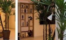 Arandela na sala de estar repleta de plantas | Projeto do arquiteto André Viana e fotos de Emerson Rodrigues